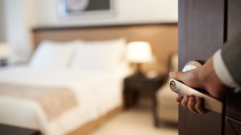 Hand an Türgriff von offener Hotelzimmertür