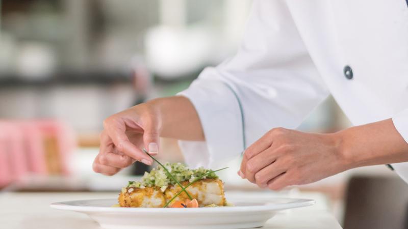 Nahaufnahme - Teller mit Gericht wird dekoriert