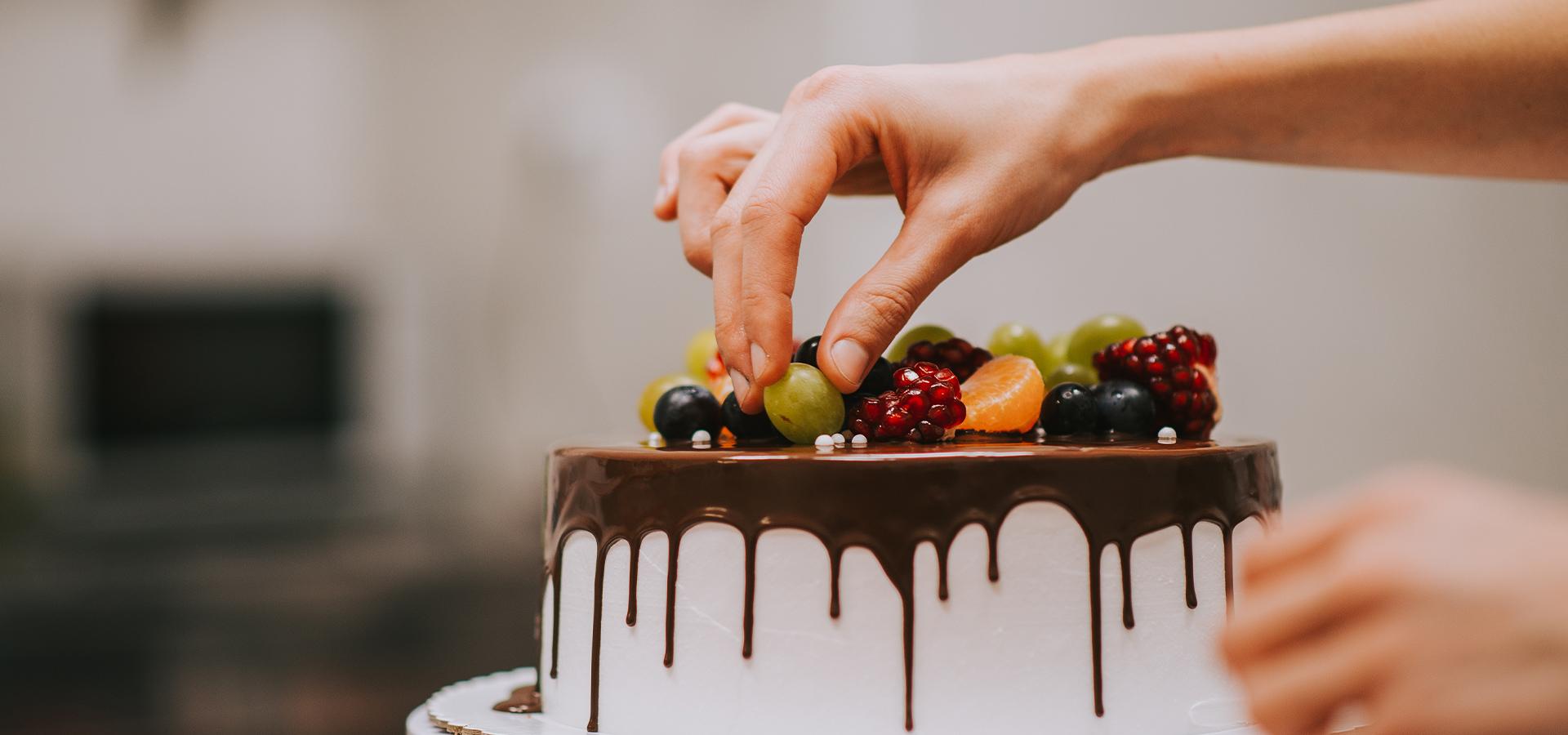 Nahaufnahme - Torte wird mit Früchten verziert