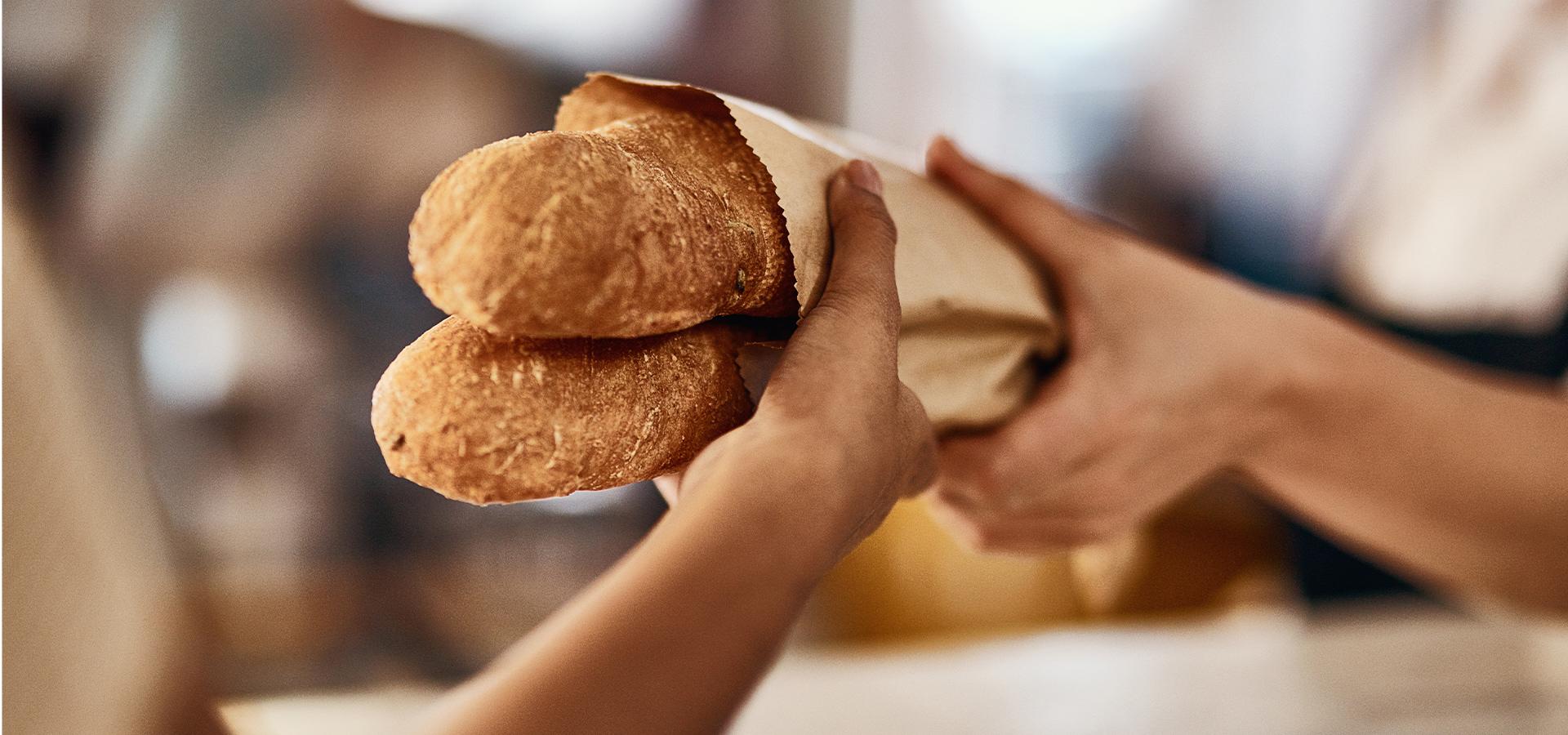 Nahaufnahme Übergabe von zwei Baguette