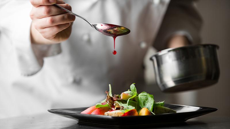 Koch mit Löffel und Topf in der Hand trägt Soße auf das Gericht auf