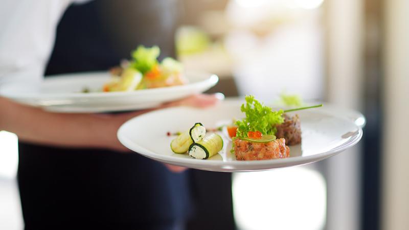 Nahaufnahme - Zwei Gerichte auf jeweils einem Teller werden von Kellnerin getragen