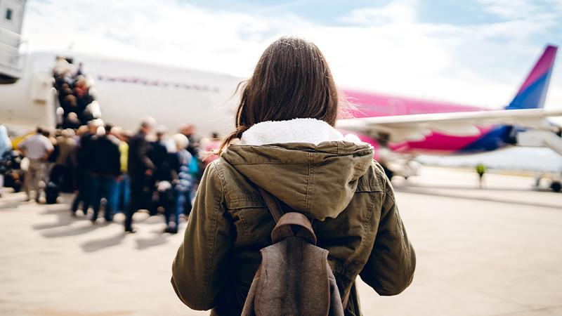 Frau auf Flugfeld beim Einstieg in ein Flugzeug