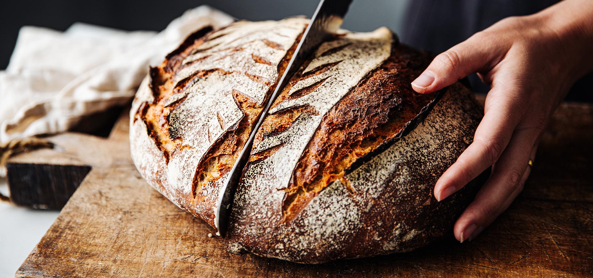 Frisches Brot wird in der Mitte durchgeschnitten