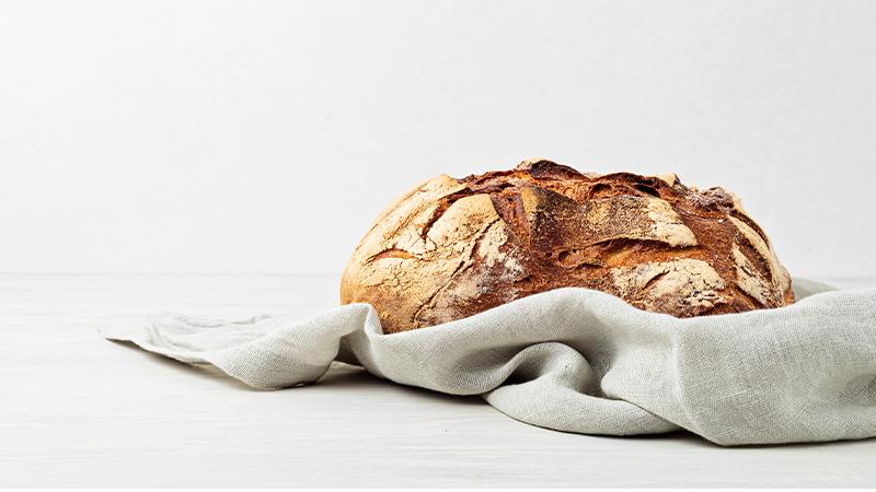 Brot auf weißem Hintergrund in Tuch gehüllt