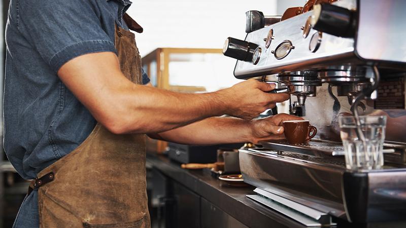 Mann arbeitet an Kaffeemaschine