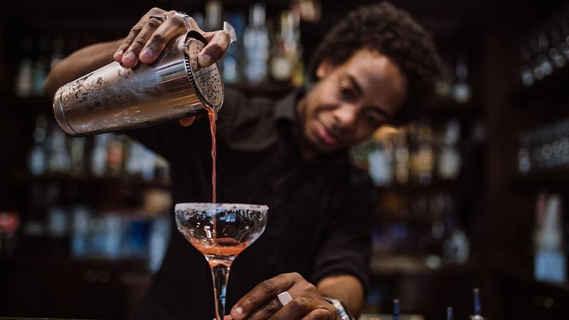 Barkeeper gießt Drink in ein Glas