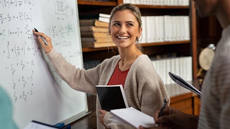 Junge Frau mit Stift in der Hand vor Tafel mit mathematischen Formeln