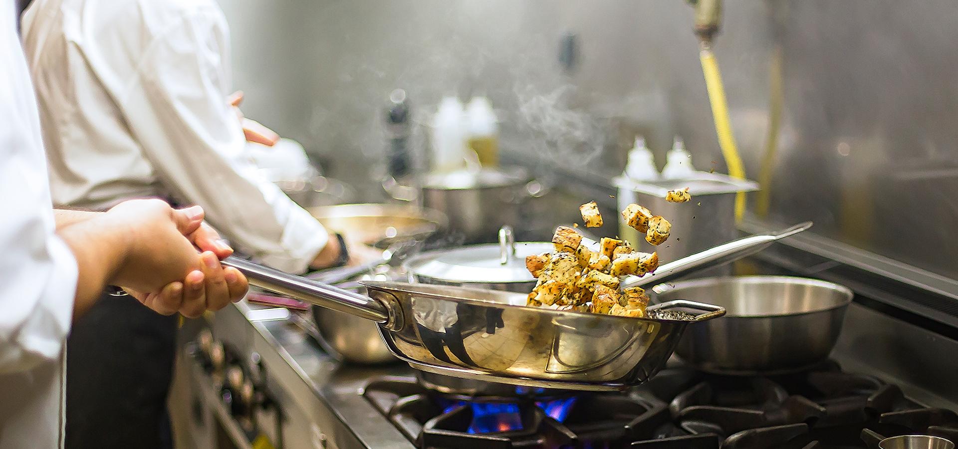 Koch schwenkt Essen in einer Pfanne auf dem Herd